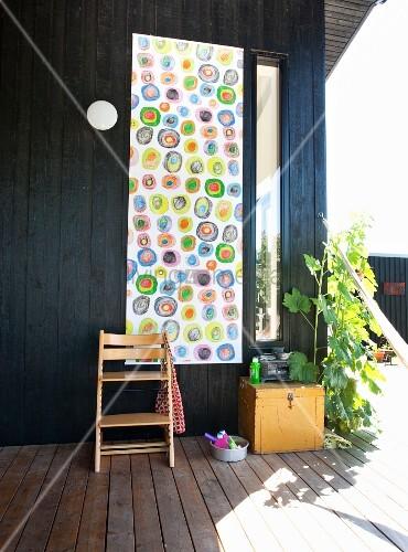 tripp trapp stuhl vor aufgeh ngtem wandbehang mit buntem kringelmuster an schwarzer holzwand auf. Black Bedroom Furniture Sets. Home Design Ideas