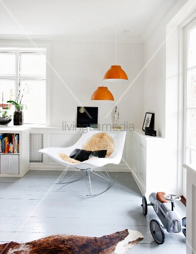 A designer rocking chair beneath orange pendant lamps in the corner of the living room with a retro toy car on grey floorboards to the side