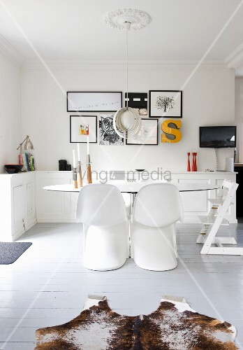 Sitzplatz mit weißen Pantonstühlen um ovalem Tisch, Designer-Pendelleuchte unter Stuckrosette in ländlichem Esszimmer