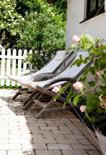 Holzliegestühle mit weißem Bezug auf Terrasse vor Wohnhaus, im Hintergrund Garten