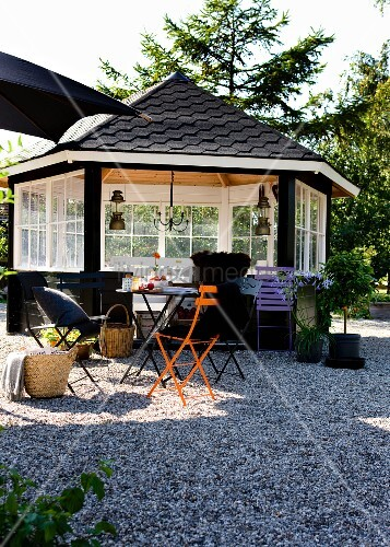 Wooden summerhouse painted black with white lattice windows behind colourful folding chairs on gravel terrace in