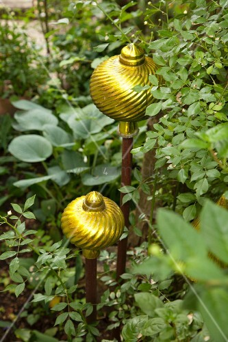 Ornate, yellow glass balls on sticks amongst plants in garden