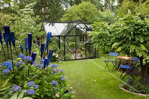 blaue st hle deko flaschen und blaue hortensien im garten mit gew chshaus bild kaufen. Black Bedroom Furniture Sets. Home Design Ideas
