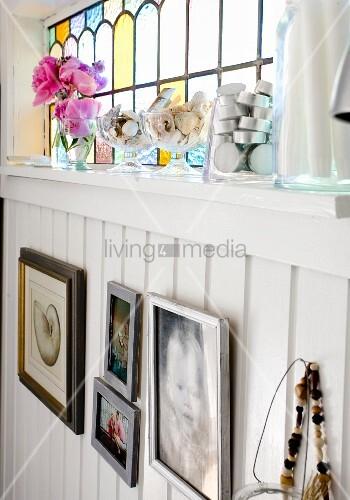 Bilder an weisser holzverkleideter Wand, oberhalb Oberlicht mit farbiger Glasfüllung, davor auf Ablage Teelichter und Glasschalen