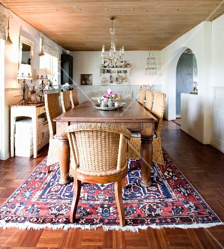 Solid wooden table and wicker chairs on Oriental rug in rustic dining room