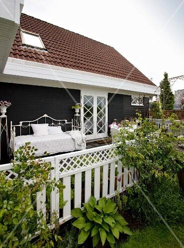 Blick von Garten auf Terrasse mit Bett aus weissem Metall vor dunkler Holzwand