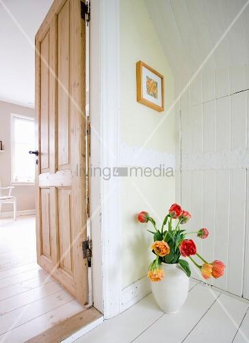 Rote und gelbe Tulpen in weisser Vase auf weiss lackiertem Dielenboden, seitlich offene Zimmertür