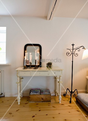 Brennende Kerzen im Kerzenhalter vor Spiegel auf Konsolentisch mit geschnitzten Beinen in Weiss, seitlich Vintage Stehleuchte aus schmiedeeisernem Gestell