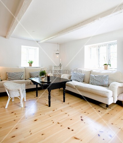 Pale sofas and white wicker chair around black coffee table in corner of rustic living room with whitewashed wood-beamed ceiling