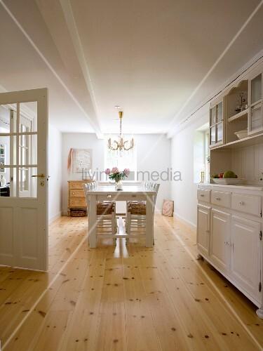 Esszimmer mit weiss lackierten Stühlen und Tisch auf gepflegtem Dielenboden, seitlich ländliche Anrichte