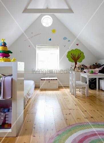Kinderzimmer in ausgebautem Dach, seitlich Regal vor Matratze auf Dielenboden, im Hintergrund Kindertisch und Stühle an Giebelwand