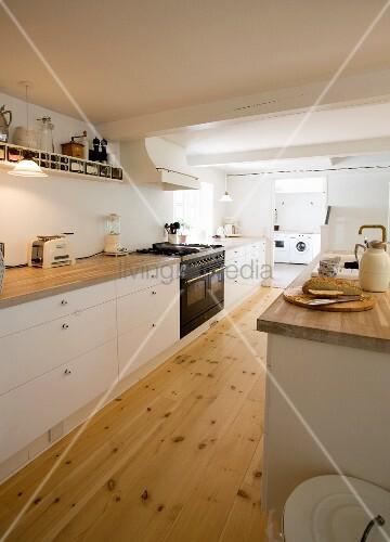 Küchenzeile mit weissen Unterschränken in grossräumiger Küche mit Dielenboden, im Hintergrund offener Durchgang zum Wirtschaftsraum