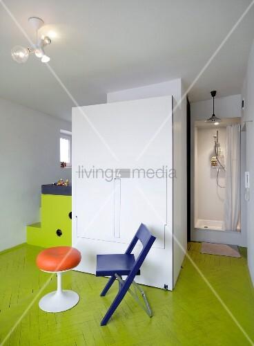 Retro-Hocker und Klappstuhl vor der geschlossenen Front einer Schrankküche auf lindgrünem Parkett; Duschkabine im Hintergrund