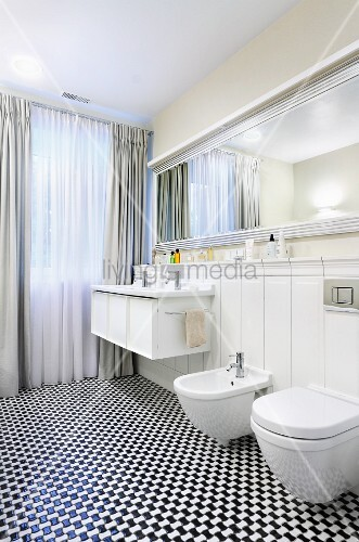 Black and white mosaic floor in elegant bathroom with classic mirror and floor-length curtains