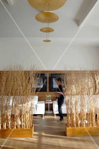 White sofas against modern, half-height wood panelling behind partitions made from bundled brushwood in wooden boxes