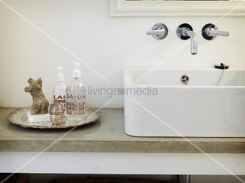 White countertop sink on stone washstand counter next to contemporary soap dispensers and miniature stone torso on vintage-style silver plate