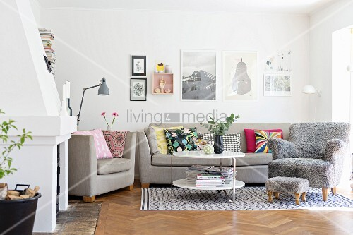 Sofa set and comfortable armchair with grey fluffy cover and matching footstool on rug in living room