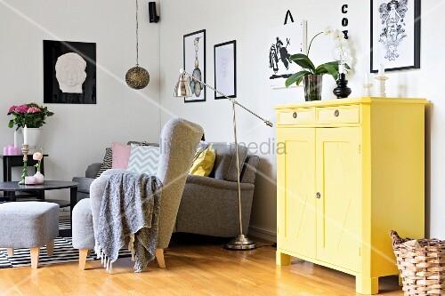 Gelb lackierte Kommode neben Sitzplatz mit grauem Polstersessel und passendem Fussschemel, Chrom Stehleuchte im Retro Stil