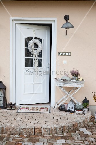 Wreath on front door and tray table on semicircular paved platform