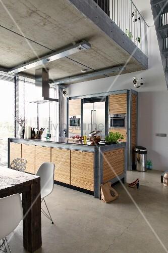 Moderner Küchenbereich unter Galerie, Theke und Schrankmöbel aus verzinktem Stahl und Zebranofurnier