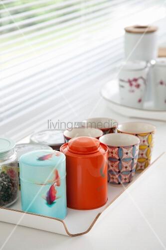Porzellanbecher und Teedosen auf Tablett vor Jalousie