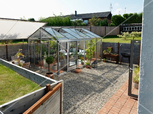 Cosily furnished retreat in greenhouse on gravel terrace in garden