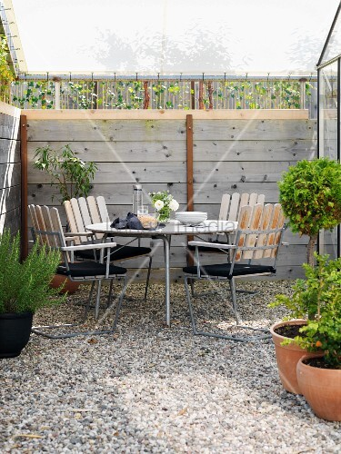 Seating area on small gravel terrace below awning with wooden frame