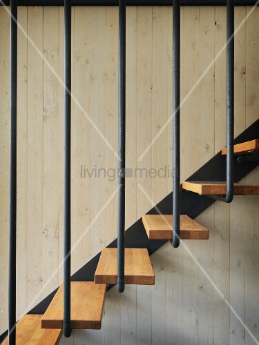 Detail of staircase with wooden treads and black metal balustrade