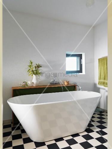 Free-standing bathtub on chequered floor in minimalist bathroom