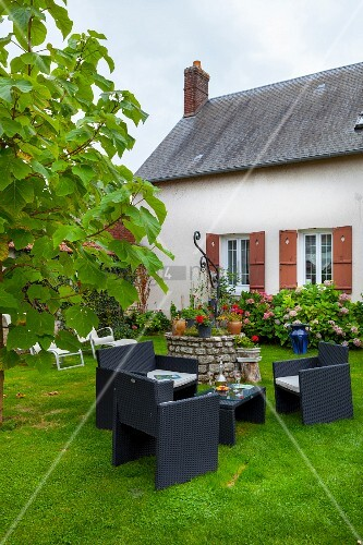 Modern outdoor furniture in front of renovated farmhouse