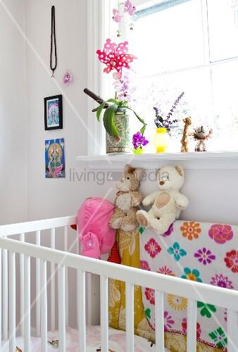 Weisses Gitterbett mit Stofftieren unter Fenster