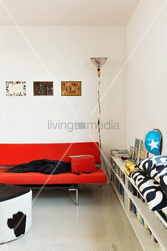 Red designer sofa next to fitted, half-height shelves in contemporary interior