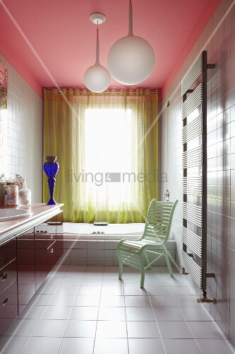 Colourful modern bathroom with pink ceiling, yellow perforated curtain, mint green chair and blue glass vase