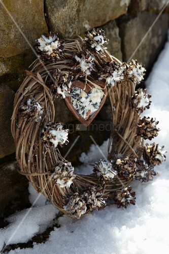 Pine cones stuffed with bird food decorating willow wreath propped up in snow