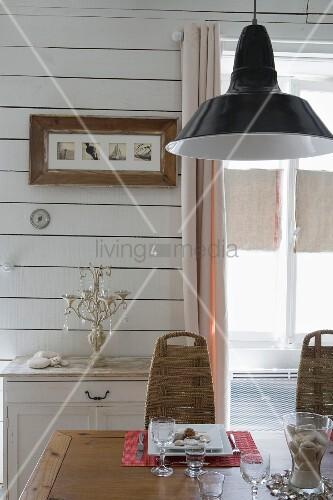 Gedeckter Esstisch auf Holz, oberhalb Pendelleuchte