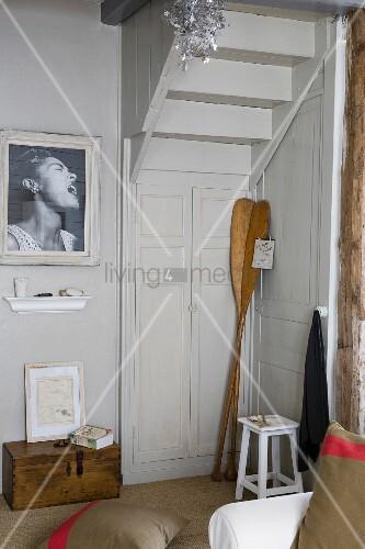 Antike Holzpaddeln in Zimmerecke unter Treppenlauf, seitlich schwarz-weisses Foto an Wand
