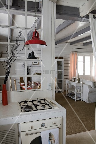 Gas hob and oven below pendant lamp with red metal lampshade below interior lattice window in partition next to open doorway with view into living room