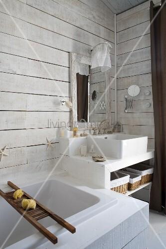 Modern bathtub next to masonry washstand in corner of bathroom with white wood-clad walls