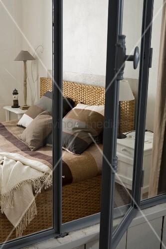 Blick durch geöffnetes Innenfenster auf Bett mit Bettwäsche in Streifenoptik und verschiedene Brauntöne
