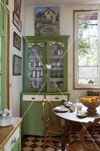 Green dresser and wooden dining table in traditional kitchen