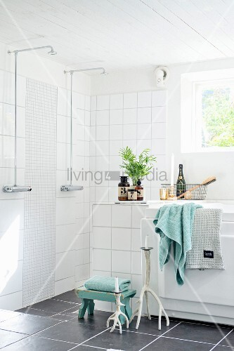 Walk-in shower area, bathtub and grey floor tiles in corner of modern bathroom