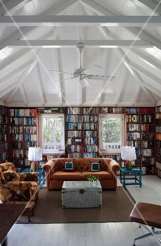 U-shaped bookcase in square room with pavilion roof structure; retro seating in natural shades in centre