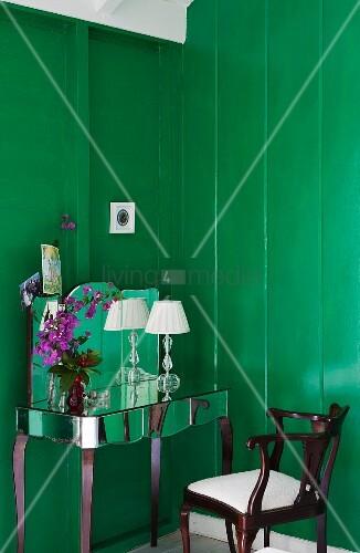Verspiegelter Schminktisch und Antikstuhl vor satt grün lackierten Holzwänden