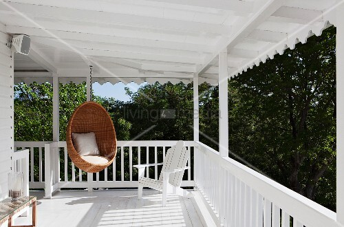 Classic Scandinavian design: wicker hanging chair by Nanna Ditzel on white veranda