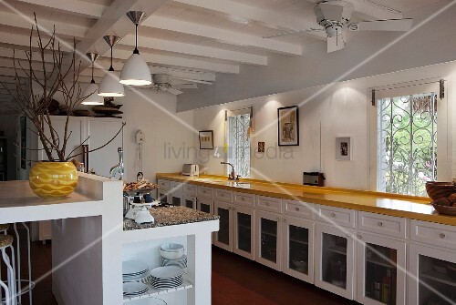 Long kitchen counter with country-house-style base units and masonry breakfast bar with crockery shelf