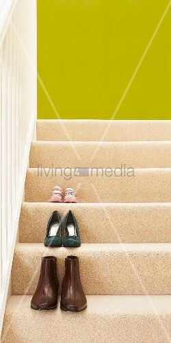 Pairs of shoes on treads of wooden staircase with cream stair carpet and spring green back wall