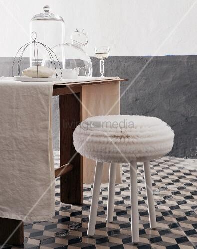 weisser hocker auf grau weissen keramikfliesen vor tisch mit glasglocken und weissweinglas. Black Bedroom Furniture Sets. Home Design Ideas