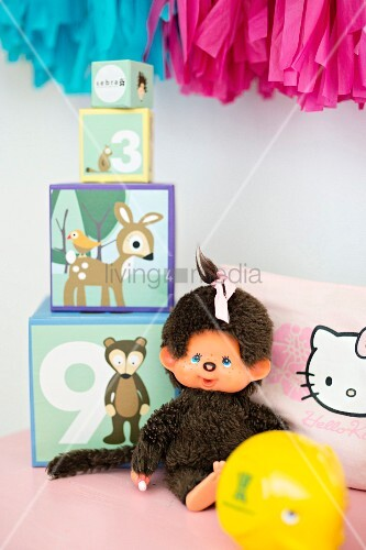 Soft toy next to stacked picture blocks of different sizes