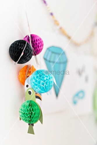Garland of colourful paper birds on wall