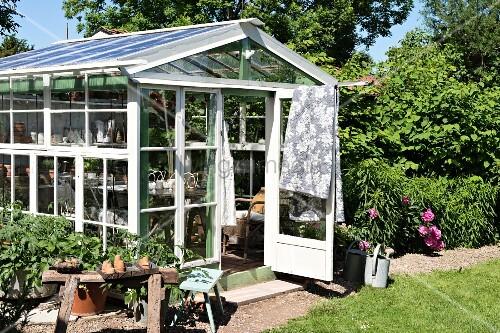 Lattice greenhouse in flowering sunny garden